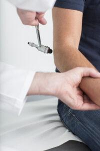 Doktor testet Ellenbogenschmerzen mittels Hammer bei der Orthopädie Dr. Ziolko in Köln